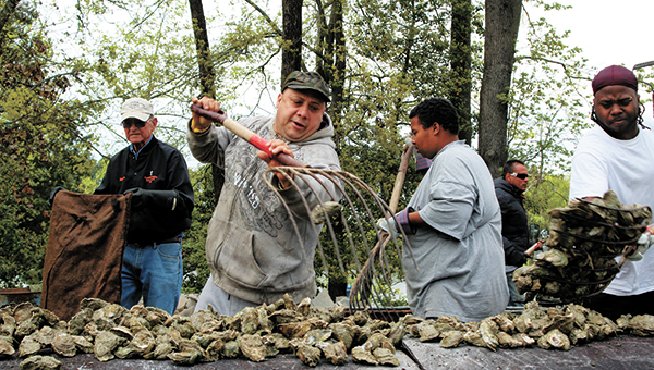 Denis Perec of Norfolk loads fresh oysters onto the pit during a previous Chuckatuck Ruritan Club Oyster Roast at Kirk Farm on Everets Road. This year's installment is set for April 8.